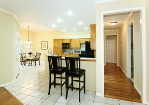 From den, view of hall, kitchen counter bar seating & breakfast nook on far left
