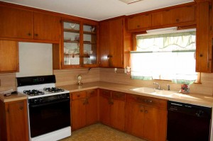 Spacious kitchen with finished wood cabinets with glass fronts; oven remains