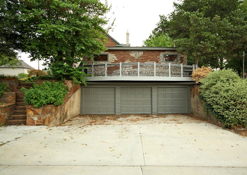 Stone steps on either side of the 3-car garage lead to ...