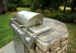 Built-in gas grill in picnic area in back yard