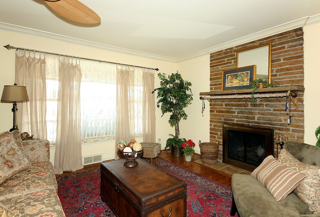 formal living with fireplace and window to south