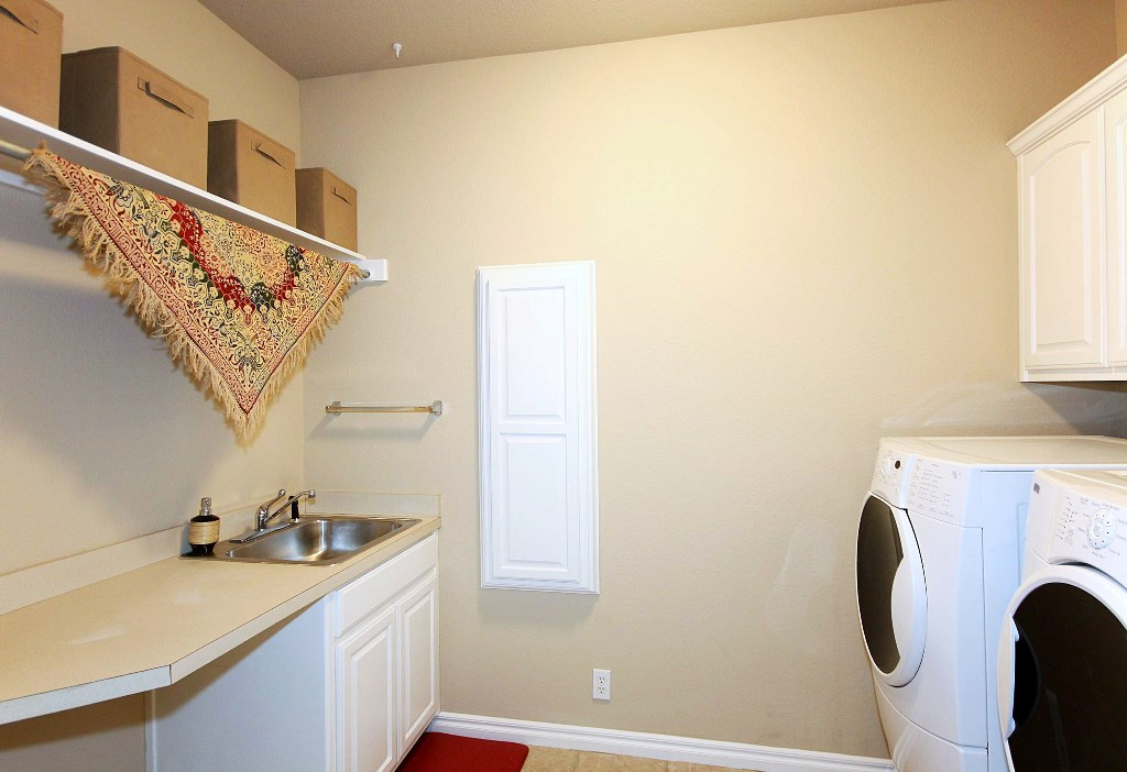 separate inside laundry with sink, cabinetry, shelving and counters