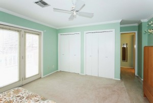 Master bedroom with double closets and doors to balcony - walk-in closet not shown