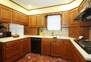 Kitchen with Corian counters, tile backsplash, brick flooring