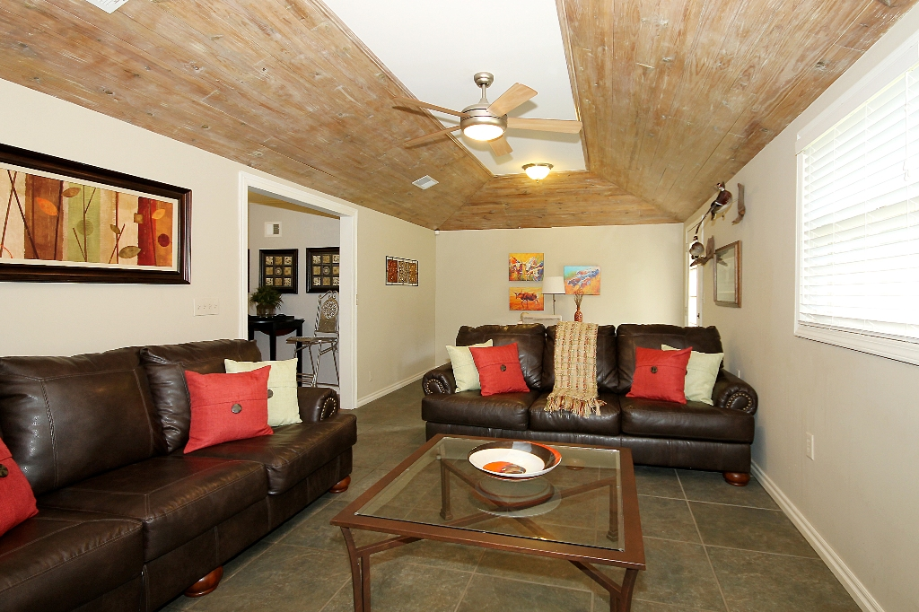 Den with slate tile flooring, new ceiling fan, much sunlight