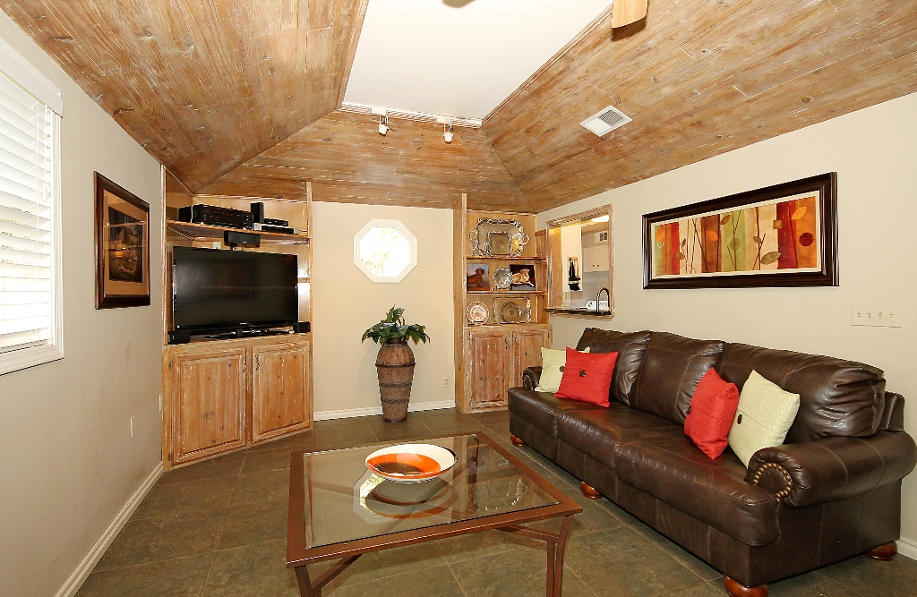 Den with vaulted ceiling and built-ins